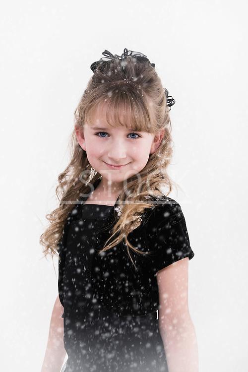 Girl (7-10) smiling in snow, portrait
