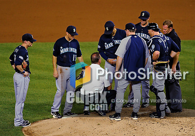 21 June 2011: Seattle Mariners pitcher Brandon League is checked by trainers after getting hit on the leg by a Michael Morse liner in the 9th inning against the Washington Nationals at Nationals Park in Washington, District of Columbia. The Nationals rallied from a 5-1 deficit, scoring 5 runs in the bottom of the 9th, to defeat the Mariners 6-5 in inter-league play. Mandatory Credit: Ed Wolfstein Photo