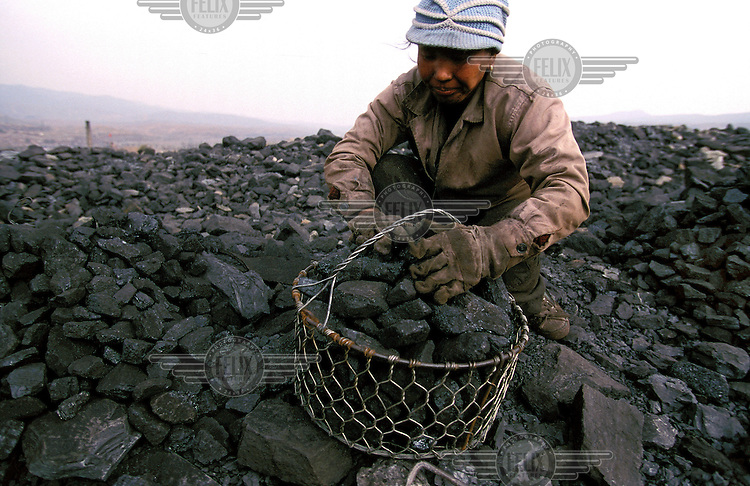 ©Mark Henley/Panos Pictures..China, Shanxi Province..Environment degradation & poverty. Peasant woman scavenging for usable fuel on coal mine slag heap that .over-shadows her village.