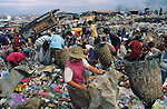 RUBBISH DUMP RECYCLING, Philippines. Poor and indigenous people, old and young, some children, work in the infamous rubbish dump 'Smokey Mountain'  outside Manilla. They recycle household and public waste, collecting and separating materials such as paper, corrugated  cardboard, metal, plastics. Many suffer chronic skin and asthmatic diseases as a result of close contact with burning rubbish and chemicals.