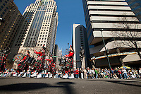 Members of the Charlotte Fire Department Pipes and Drum Band , make their way through the intersection of Trade and Tryon Street in front of the watchful eyes of Thousands of people who turned out to watch the annual St. Patrick's Day Parade in Uptown/Downtown Charlotte, North Carolina.