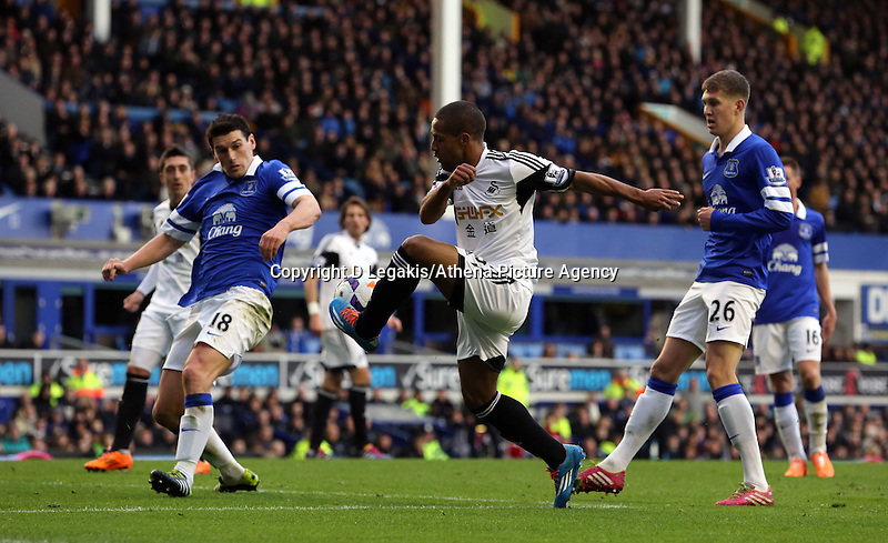 Pictured: Wayne Routledge of Swansea (C) attempts to cross the ball against Gareth Barry (L) and John STones (R) of Everton. Saturday 22 March 2014<br /> Re: Barclay's Premier League, Everton v Swansea City FC at Goodison Park, Liverpool, UK.
