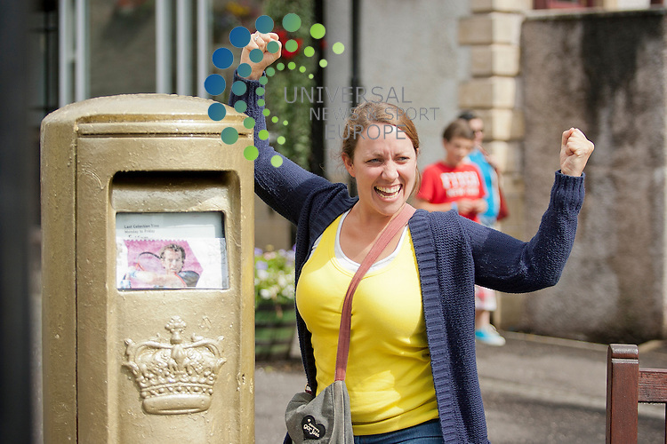 A local resident celebrates next to a post box painted gold to celebrate Andy Murray's win at the London 2012 Olympic Games. Monday, August 06, 2012.  ..Picture: Malcolm McCurrach, Universal News and Sport (Europe) - 06/08/2012