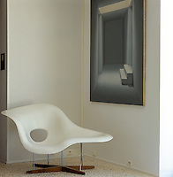 An Eames chair stands beneath a stark painting in the corner of a pebble-floored room