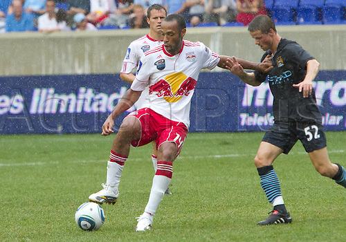 25 JULY 2010:  New York Red Bulls forward Thierry Henry (14) dribbles ball and pushes away Manchester City midfielder Andrew Tutte (52) during international friendly match in the Barclays New York Challenge between Manchester City and the New York Red Bulls. New York won the game 2-1.