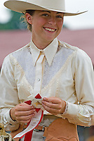 A smiling girl wearing a white hat and lace blouse smiles and hlds her red ribbon after a horse competition at the Knox County Fair in Mt. Vernon, Ohio.<br />
