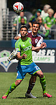 Seattle Sounders' Lamar Neagle eyes the ball while being guarded by Colorado Rapids' Thomas Piermayr during an MLS match on April 26, 2014 in Seattle, Washington.  Neagle scored one goal in the Seattle Sounders 4-1 win 0ver the Colorado Rapids.  Jim Bryant Photo. ©2014. All Rights Reserved.