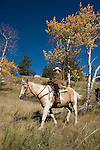 Family group outdoors on a crisp and cool fall morning riding horses on a wrangler-led ride, amid aspen groves high in Rocky Mountains, near Estes Park, Colorado, USA