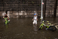 10 year-old Kai Galvan-Dubois (L) and his brother 6 year-old Crois Galvan-Dubois play in a rain water flooded section of 12th Avenue in Hamilton Heights, New York City, NY, USA shortly after tropical storm Irene passed over the city, 28 August 2011.