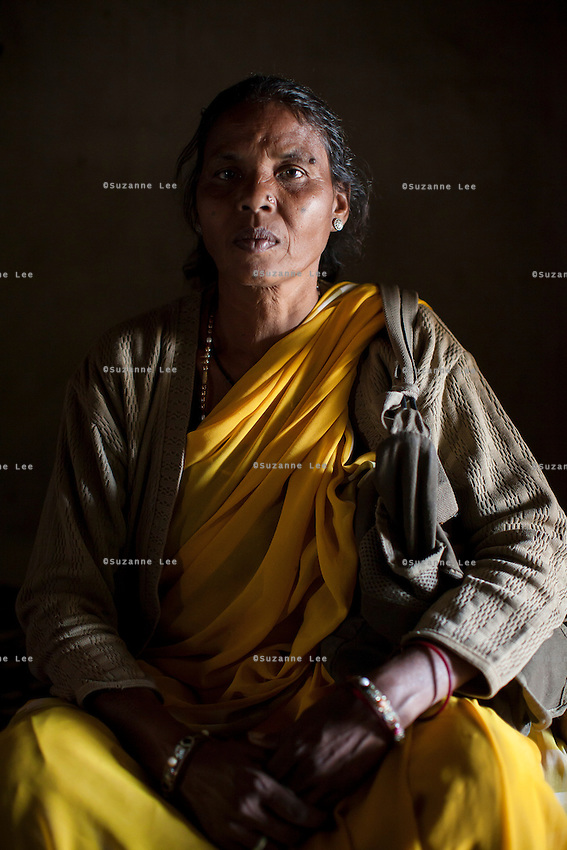 Community reporter Shanti Adivasi, 52, sits for a portrait in a village house in Manikpur, Chitrakoot, Uttar Pradesh, India on 6th December 2012. Shanti used to be a wood gatherer, working with her parents since she was 3, and later carrying up to 100 kg of wood walking 12km from the dry jungle hills to her home to repack the wood which sold for 3 rupees per kg. After learning to read and write in an 8 month welfare course, at age 32, she became a reporter, joining Khabar Lahariya newspaper since its establishment in 2002, and making about 9000 rupees per month, supporting her family of 14 as the sole breadwinner. Photo by Suzanne Lee for Marie Claire France.