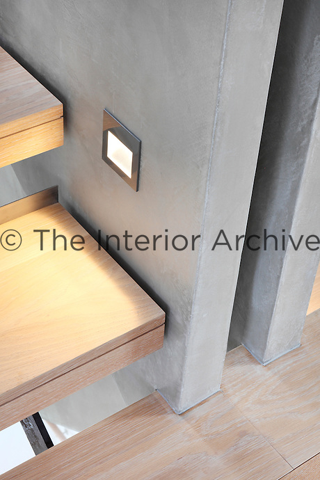 A detail of a modern staircase with wooden treads. A square low level light is embedded in the concrete side panels.