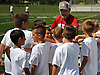 A group of nine-year-old children gathers with Joe Vito, head coach of Roosevelt varsity football, during the Long Island Youth Football Player Academy at Cedar Creek Park in Seaford on Monday, July 11, 2016.