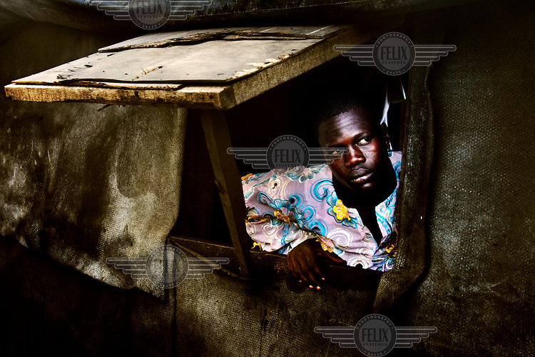A man looks out from his house at the Olusosun landfill site. The Olusosun dump is Nigeria's largest trash heap comprising over 100 acres of garbage and is believed to be the largest in Africa. There are around a thousand houses built within its boundaries.