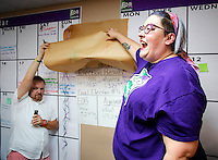 NWA Democrat-Gazette/DAVID GOTTSCHALK  Shannon Hix (left), campaign manager, is helped by Laura Phillips, treasurer, as they reveal Tuesday, September 8, 2015 the results of the passing of the Uniform Civil Rights Administration ordinance at the campaign headquarters for For Fayetteville.