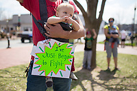 NWA Democrat-Gazette/CHARLIE KAIJO Colton Lindeman of Fayetteville demonstrates as he holds Cooper Lindeman, 10 months, in a carrier during the &quot;March For Our Lives&quot; rally, Saturday, March 24, 2018 at the Bentonville Square in Bentonville. <br /> <br /> &quot;He&rsquo;s so young. This is the first rally like this we&rsquo;ve gone to,&quot; said Lindeman about why he brought his son. &quot;He can grow up to be anything he wants. Hopefully this will open him up to this kind of event.&quot; <br /> <br /> &quot;[We're here] just to get everyone together and on the same page and talk about solutions to gun laws and how we can make a change,&quot; Lindeman added.<br /> <br /> &ldquo;March For Our Lives&rdquo; is a march against gun violence. &quot;[We're] just a group of kids who got together one day and wanted to make a change,&quot; said Taylor Gibson, 16, a student at Bentonville West High School. She is one of nine students from area high schools including Bentonville West, Bentonville High, Gravette and Haas Hall who organized the rally. The rally is in solidarity with more than 800 protests around the world according to &quot;March For Our Lives&quot; organizers
