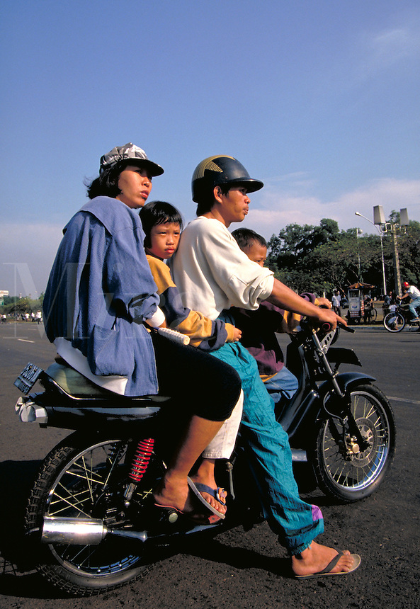 Motorcycles offer Indonesian families an affordable method of transportation in Jakarta. activities, parents, children. Indonesian family in Jakartaa. Jakarta, Indonesia central city.