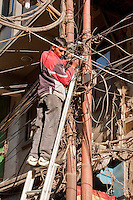 Kathmandu, Nepal.  An Electrician Works on an Electrical Connection in the Center of Kathmandu.  Is this a high-risk occupation?  Electric wiring suggests that electrical service has grown in a jury-rigged manner over time, with no master plan.