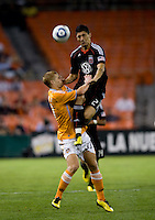 Pablo Hernandez (21) of DC United goes up for a header against Andrew Hainault (31) of the Houston Dynamo during their game at RFK Stadium in Washington, DC.  Houston defeated D.C. United, 3-1.