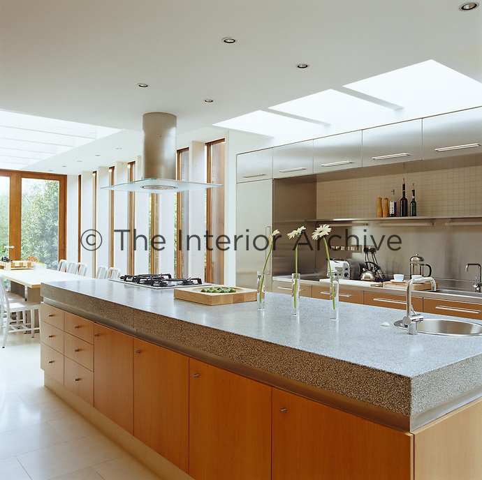 This kitchen is dominated by a long granite-topped island echoing the shape and size of the dining table beyond