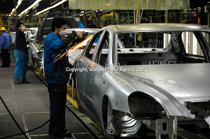 Chinese labourers work on an assembly line for Brilliance Zhonghua Junjie at Brilliance Auto in Shenyang, Liaoning province, China.  .21 Nov 2006