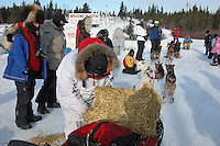 Paul Gebhardt uses string to tie straw to his sled bag before blowing through Koyuk. Photo by Jon Little.