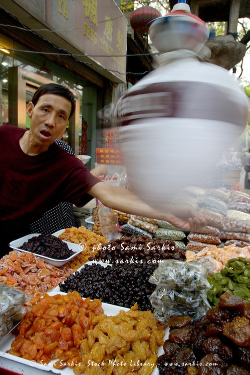 Man selling dried fruit at the market, Daqingzhen Si, Muslim District, Xian, Shaanxi, China.