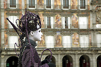 Spain. Province of Madrid. Madrid. Plaza Mayor ( Mayor place). A woman is dressed up as a queen. She wears purple clothes and her face is made up white. She stands stock-still and is making her living as a mime. Downtown. Town center. © 2007  Didier Ruef