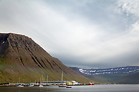 Boats at dock in Isafjordur below Kirkjubolsfjall mountain, West Iceland, Iceland