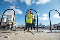 STAFF PHOTO ANTHONY REYES &bull; @NWATONYR<br /> Dan Howell, checks the height of a section of fence as coworker Sean Dagestad, both with the Rogers Street Department, looks on Monday, Dec. 15, 2014 as they install a fence along a sidewalk on south First Street in Rogers. The pair were making sure all the pieces were plumb and level before permanently attaching the pieces.The fence will help people climb a tall curb and to keep them from falling down in accidentally.