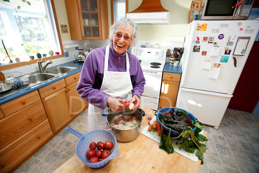 Wendy Morton, 69, an insurance investigator and published poet, saves money by growing her own vegetables, fruit, and herbs, baking her own bread, making her own soups and meals with garden produce, shopping at thrift stores, and air-drying her laundry on the clothesline at her beautiful acreage home in Sooke, British Columbia, on Vancouver Island. Photo assignment for the Globe and Mail national newspaper in Canada.