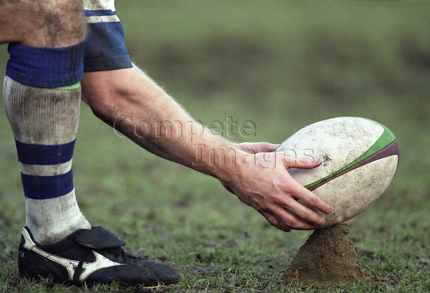 Rugby player placing rugby ball on soil tee