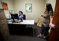 NWA Democrat-Gazette/JASON IVESTER <br /> Kellye Beavers (right), Career Services NWA manager, talks on Wednesday, Aug. 12, 2015, Denise King, data management specialist, inside the center in Rogers.