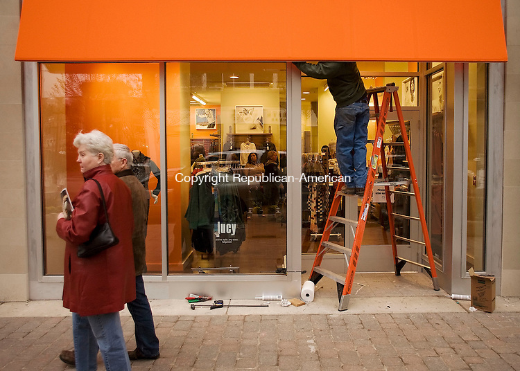 WEST HARTFORD, CT--12 November 07--111207TJ12 - Pedestrians pass by a store that recently opened in the Blue Back Square mall in West Hartford, Conn., as a worker puts finishing touches around the entrance on Monday, November 12, 2007. A number of stores recently opened, while other shops, office buildings, and a condo complex remian under construction. T.J. Kirkpatrick/Republican-American