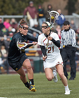 Boston College midfielder Caroline Margolis (21) on the attack as University of Maryland midfielder/defender Megan Douty (5) defends..University of Maryland (black) defeated Boston College (white), 13-5, on the Newton Campus Lacrosse Field at Boston College, on March 16, 2013.