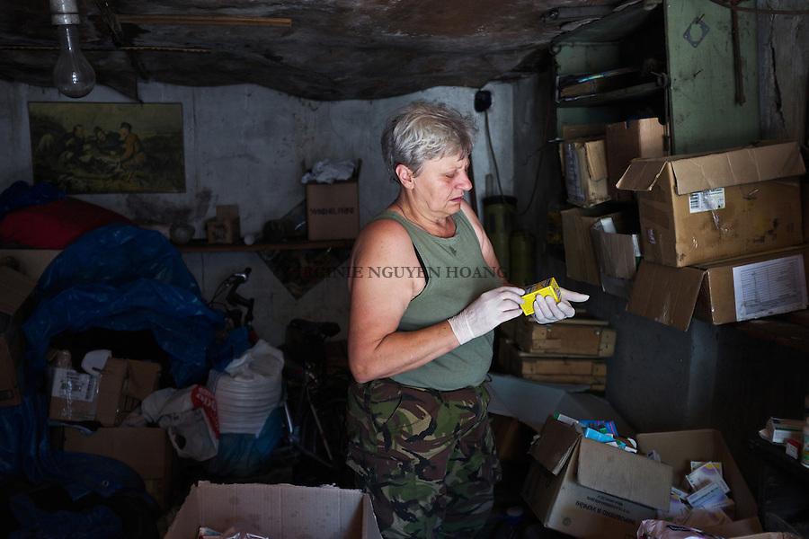 UKRAINE, Pisky: Mama is making some order in her warehouse. She likes that everything is clean and tide up but sometimes it's hard as it's war zone. <br /> <br /> UKRAINE, Pisky: Mama fait un peu d'ordre dans son entrep&ocirc;t. Elle aime que tout soit en place et propre, mais c'est parfois difficile en zone de guerre.