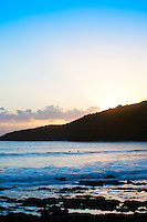 Surfers brave the chilly waters at Langland bay for an evening surf as the sunset goes down in Swansea.