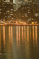 East River at Night, Illuminated Manhattan Buildings in the background, in soft focus, New York City