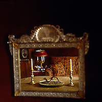 The cloth-covered dining table and a richly upholstered sofa are reflected in the glass of a gilt-framed mirror