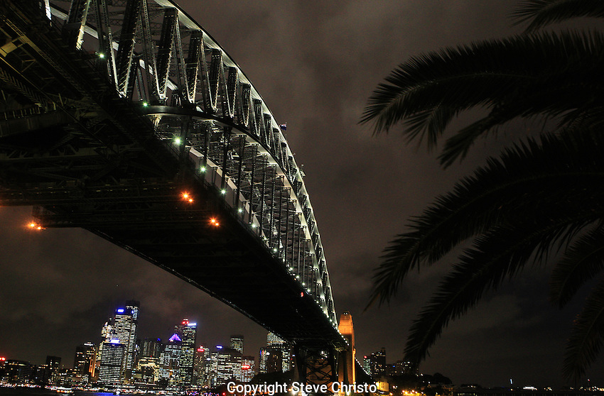 Storm clouds gather over the Sydney Harbour Bridge on sydney harbour at night. Sydney, Australia. Wednesday 6th June 2012. (Photo: Steve Christo).