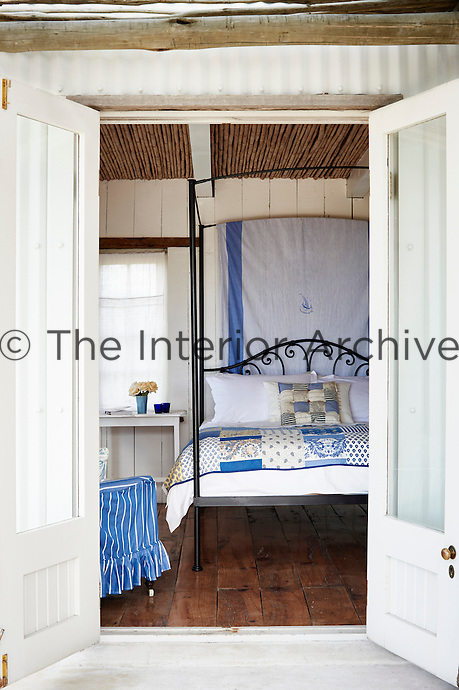 A view through a pair of open doors into a country bedroom. The room is furnished with an iron four-poster bed with a blue and white bed cover.