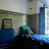In a corner of the blue and white bedroom the walls are partly lined with decorative tiles and an upholstered daybed stands in front of the window