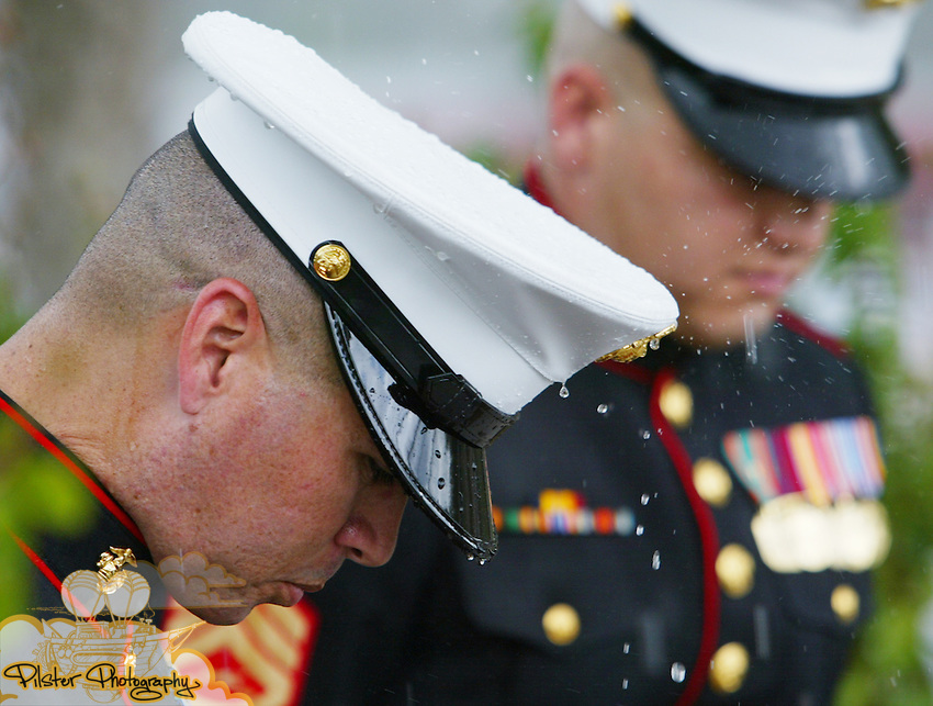 Staff Sergeant Elis CruzRivera <cq>, a marine recruiter, bows his heads for a moment of prayer as the rain comes down Saturday, June 30, 2007, during the official opening of the traveling Vietnam Memorial Wall and a Patriotic Picnic at Rotary Park in Orange City. The wall is in the northeast corner of Orange City's Rotary Park. The wall is part of the Vietnam and All Veterans of Brevard and is a 3/5th replica that was unveiled to the public in April of 2006. There are five moving walls in country that are replicas of the wall in Washington D.C. Greg Welsh <cq>, from Cocoa, is the wall manager and travels everywhere the wall does to help set it up and maintain it. The picnic was so Rotary Park can change it's name to the Veterans Memorial Park. (Daytona Beach News-Journal, Chad Pilster)