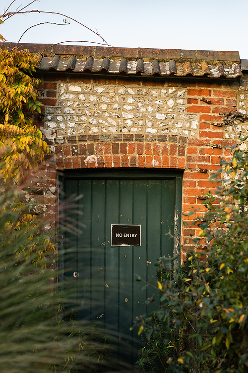 Green door in a flint garden wall