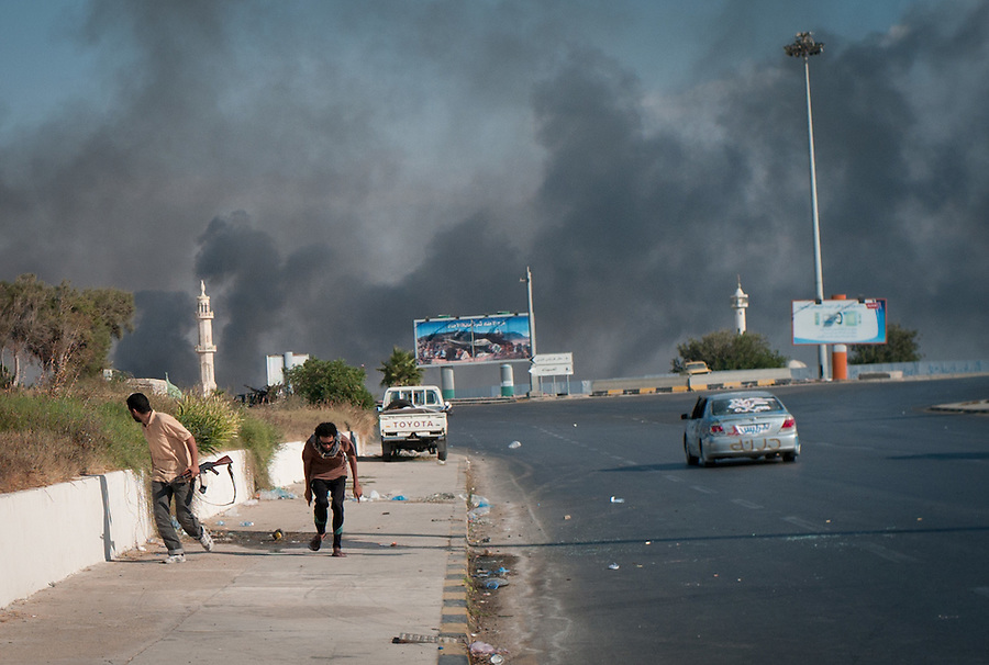 Rebel fighters take cover from incoming sniper fire near the Bab Al Aziziya compound in Tripoli, Libya