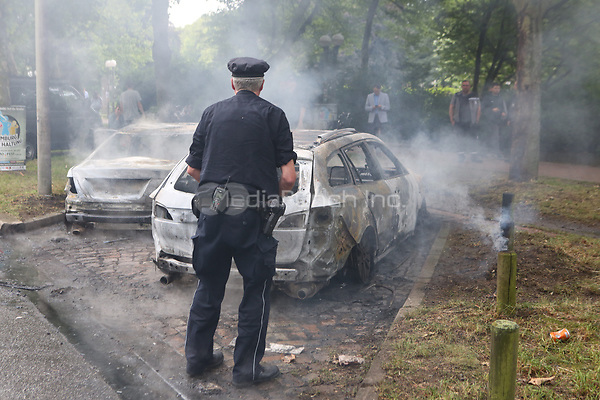 A police officer looks at a burnt-out car during demonstrations against the G20 summit in Hamburg, Germany, 7 July 2017. The summit, a meeting of the governments of the twenty largest world economies, begins on the 7 July and concludes on the 8 July. Photo: Bodo Marks/dpa /MediaPunch ***FOR USA ONLY***