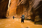 Two young men hike the Virgin River Narrows in Zion National Park, Utah.