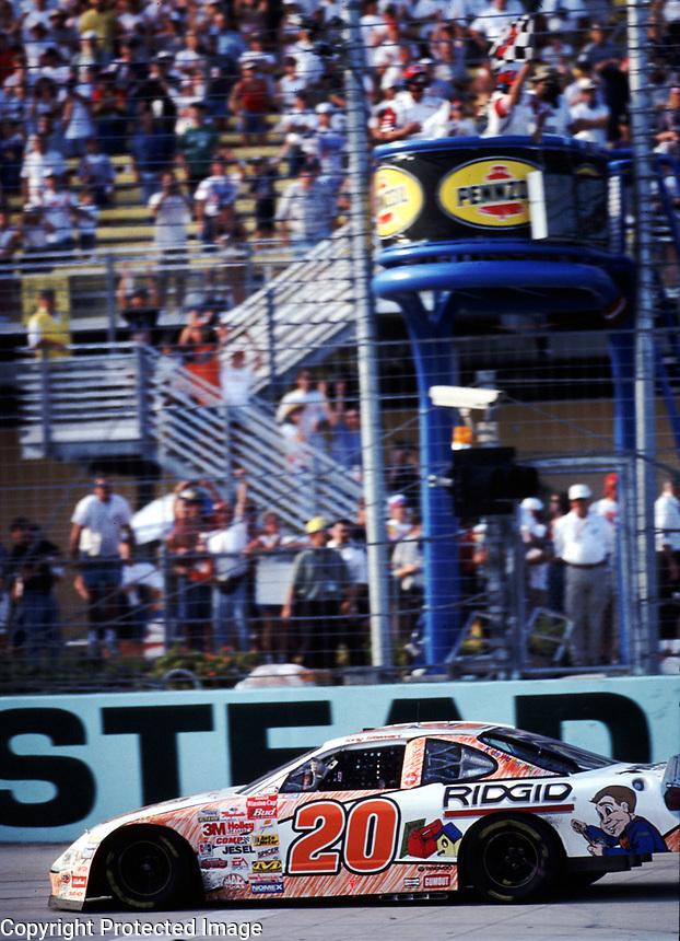 Tony Stewart takes the checkered flag to win the Pennzoil 400 at Homestead-Miami Speedway on 11/12/00.(Photo by Brian Cleary)
