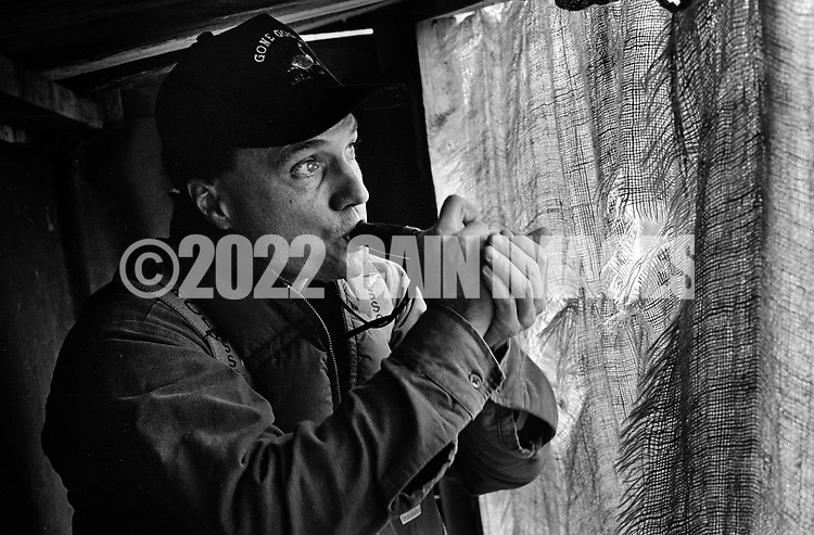 While sitting behind the blind, Bill lewis calls geese with a goose call Saturday November 2, 1991 in Buckingham, Pennsylvania. (Photo by William Thomas Cain)