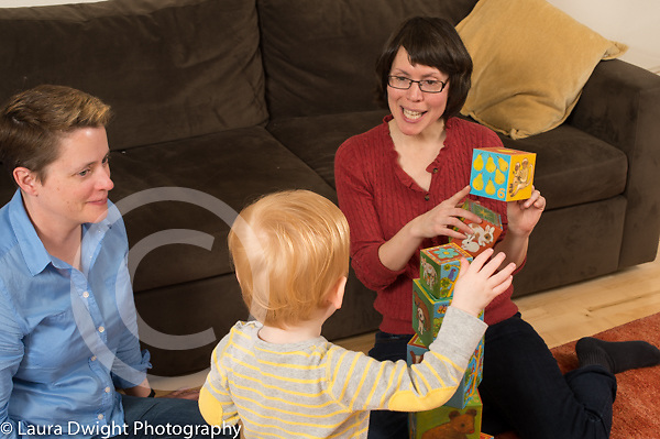22 month old toddler boy at home with mothers playing with stacking blocks