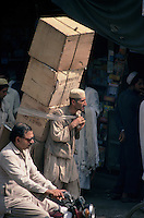 A porter struggles through the people and traffic of a street in Peshawar carrying a stack of boxes on his back.
